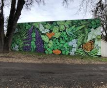 street view of a mural with green leaves, butterflies, and purple flowers