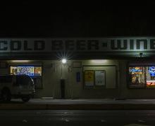 color photograph of a liquor store at night