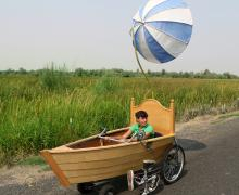a sculpture of a boat on wheels pedalled by the artist