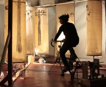 Artist seated inside installation pedals and powers spinning scrolls showing power lines.