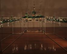 Large clear sculptural installation on warm wood floor with mechanical parts