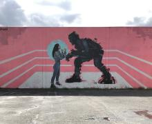 street view of a mural with a woman and a monster together in a boxing ring