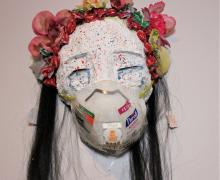 white face mask with black hair and red flowers
