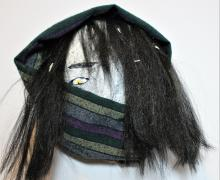 white mask with black hair and black scarf wrapped around face