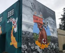 large colorful mural on a building showing a man in Pomo costume