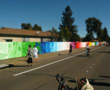 long shot view of colorful mural painted onto 500' fence